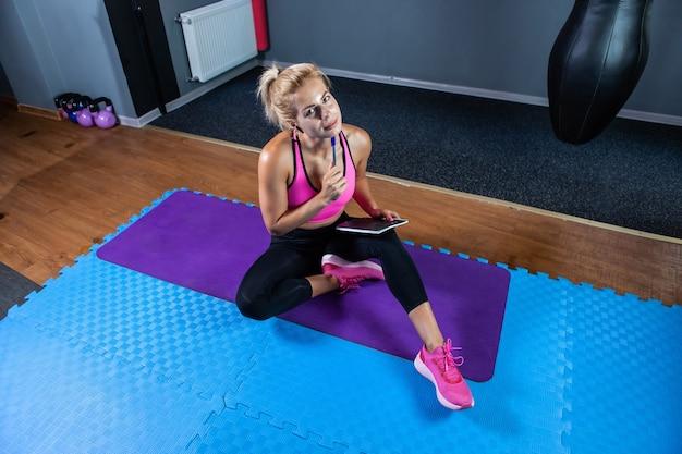 Kaukaska blond fitness kobieta zastanawia się i zapisuje w zeszycie treningowym plan treningu, siedząc na macie w klasie fitness.