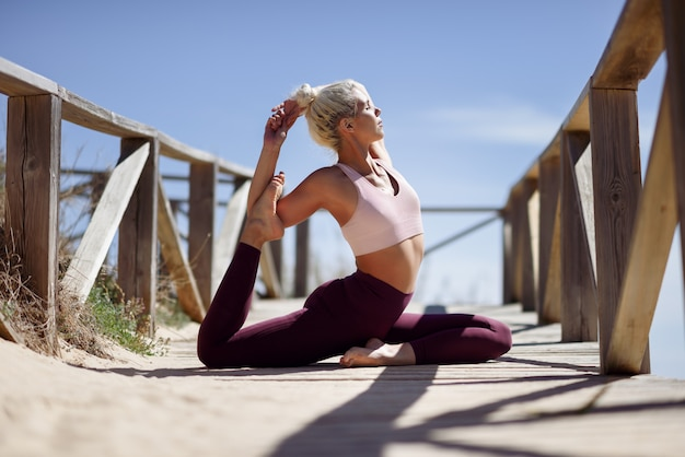 Kaukaska blondynki kobieta ćwiczy joga na plaży