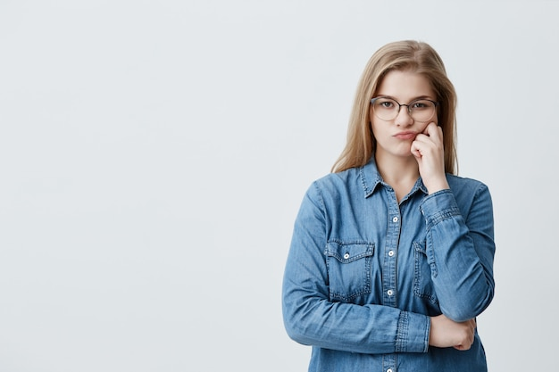 Kaukaska blondynki ładna kobieta w dżinsowej koszula w okularach wydyma usta z niezadowolenia, gdy wątpi. rozważna dziewczyna krzyżuje ramiona z rozczarowaniem i obrazą