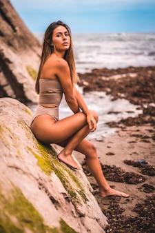 Kaukaska brunetka w brązowym stroju kąpielowym nad morzem