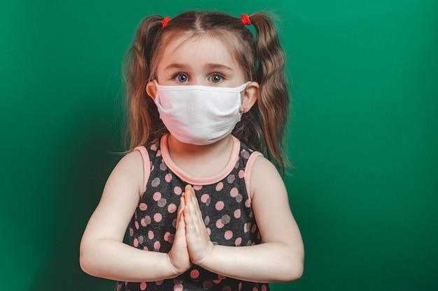 Kaukaska chora dziewczynka w masce medycznej podczas epidemii koronawirusa modli się na zielonym tle zbliżenie 2021