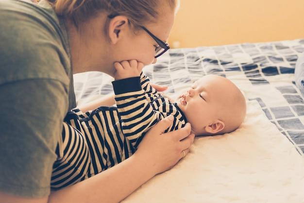 Kaukaska czuła mama i maluch leżą na łóżku, delikatnie dotykają maluszka, pojęcie macierzyństwa, zaufania i ochrony. styl życia i lekkie ujędrnienie