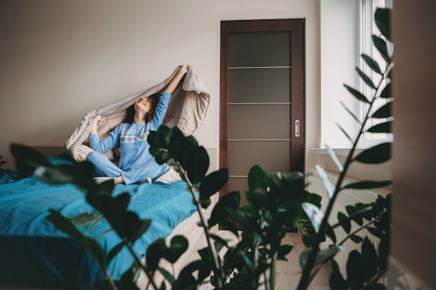 Kaukaska dama budząca się z łóżka ubrana w niebieską piżamę, uśmiechnięta i wyciągająca się z kołdrą