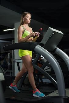Kaukaska dziewczyna biega na karuzeli trzyma jej telefon komórkowego w gym