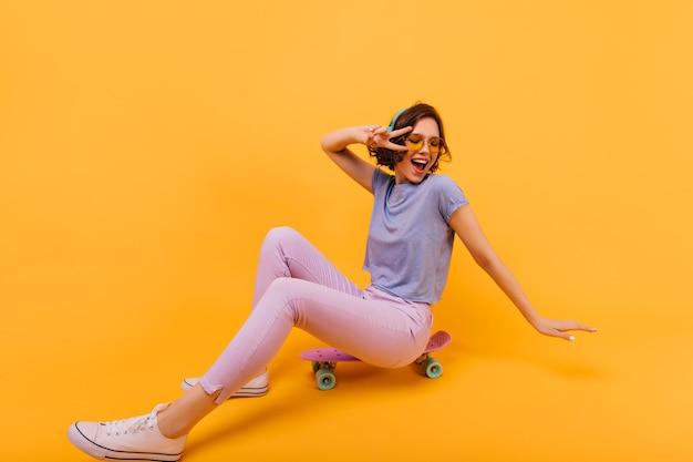 Kaukaska dziewczyna debonair siedzi na deskorolce w białych butach. śmiejąca się ładna pani w słuchawkach pozowanie.