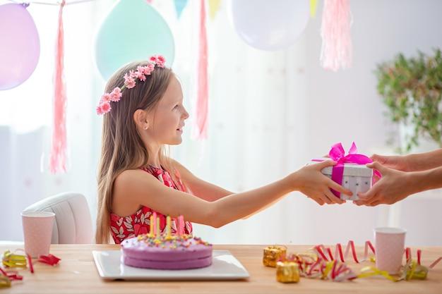 Kaukaska dziewczyna marzycielsko uśmiecha się i patrząc na urodzinowy tort tęczowy. świąteczne kolorowe tło z balonów. koncepcja przyjęcie urodzinowe i życzenia.