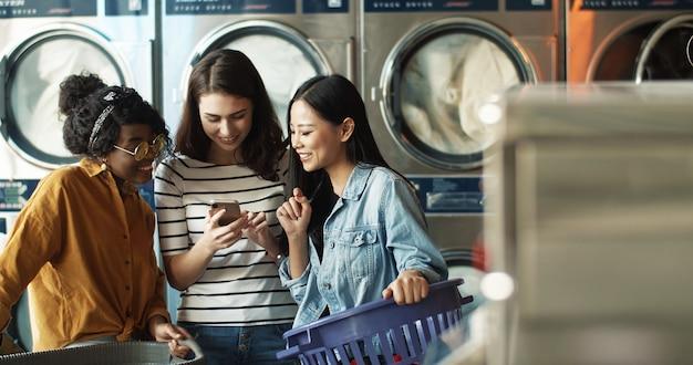 Kaukaska dziewczyna pokazuje zdjęcia na smartfonie mieszanym rasom koleżankom, podczas gdy pralki pracują i sprzątają ubrania. wieloetniczne kobiety oglądają wideo na telefonie w pralni.