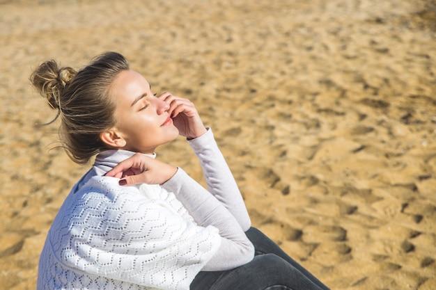 Kaukaska dziewczyna siedzi na piasku nad morzem, zamykając oczy i ciesząc się wycieczką do natury.