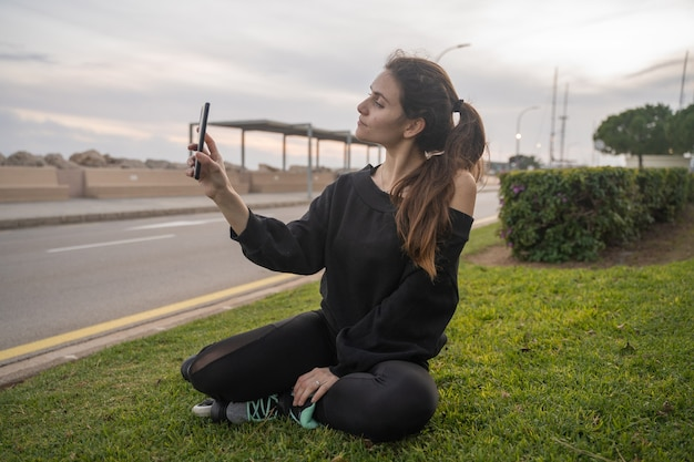 Kaukaska dziewczyna siedzi na trawie z łyżwami podczas robienia selfie smartfonem o zachodzie słońca