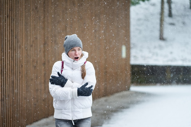 Kaukaska dziewczyna w białej kurtce robi się chłodna i próbuje się ogrzać w śniegu