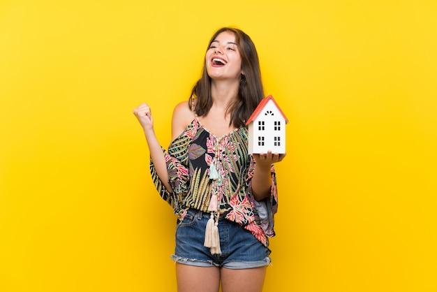 Kaukaska dziewczyna w kolorowej sukni nad odosobnioną kolor żółty ścianą trzyma małego dom