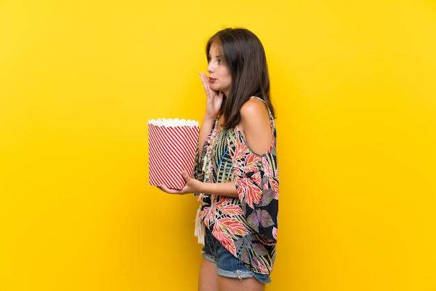 Kaukaska dziewczyna w kolorowej sukni nad odosobnioną kolor żółty ścianą trzyma puchar popkorny