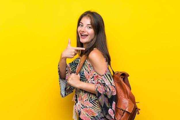Kaukaska dziewczyna w kolorowej sukni nad odosobnioną kolor żółty ścianą z plecakiem