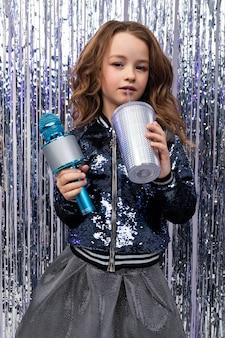 Kaukaska dziewczyna w konkursie talentów z mikrofonem i szklanką napoju na błyszczącej ścianie