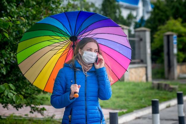 Kaukaska dziewczyna w masce ochronnej stoi na pustej ulicy na przystanku autobusowym pod parasolem w wiosennym deszczu i rozmawia przez telefon.