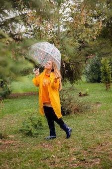 Kaukaska dziewczyna w żółtym płaszczu przeciwdeszczowym spacerująca na zewnątrz w deszczowy dzień jesienią ludzie jesienią