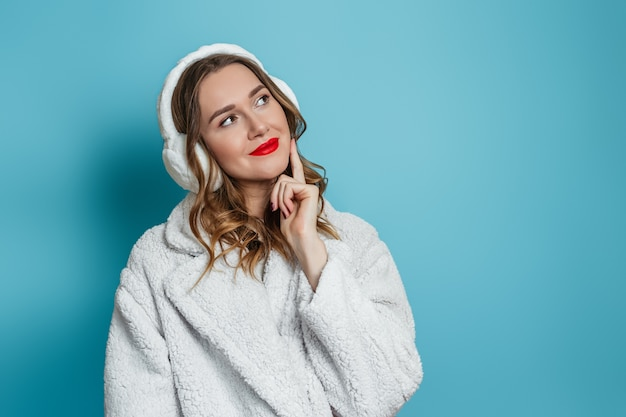 Kaukaska dziewczyna z czerwoną szminką ubrana w biały zimowy płaszcz ze sztucznego futra i futrzane słuchawki jest zamyślona i spogląda z boku na miejsce na tekst na niebieskiej ścianie