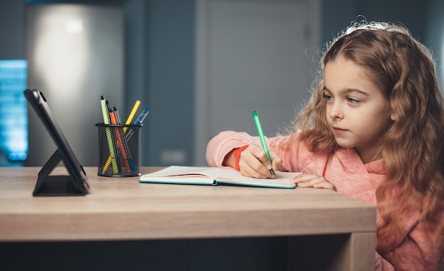 Kaukaska dziewczyna z falującymi włosami zapisuje informacje, słuchając nauczyciela z tabletu