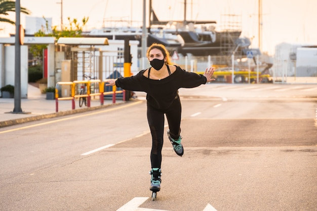 Kaukaska dziewczyna z maską na łyżwach o zachodzie słońca