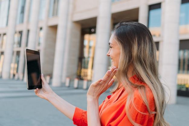 Kaukaska dziewczyna za pomocą tabletu i rozmawia czat wideo i wita się.