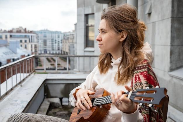 Kaukaska hipster / hipis kobieta w przypadkowych ubraniach grająca na hawajskiej gitarze, śpiewa piosenkę na ukulele podczas samowyizolacji w domu na tarasie.