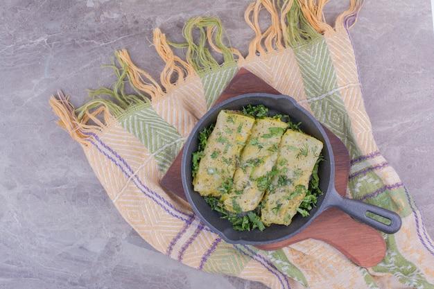 Kaukaska kapusta zawija się z mielonymi ziołami na czarnej patelni.