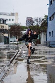 Kaukaska kobieta bawi się wodą z deszczu na drodze