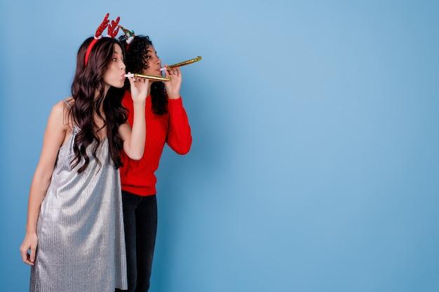 Kaukaska kobieta i czarna dziewczyna wieje świąteczne gwizdki
