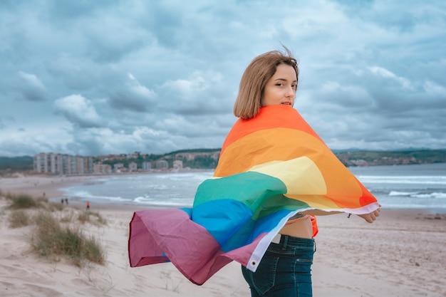 Kaukaska kobieta lesbijka na plaży trzyma tęczę flaga duma - wizerunek