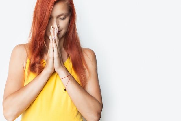Kaukaska kobieta modli się na białej ścianie studia trzymając dłonie razem i zamykając oczy