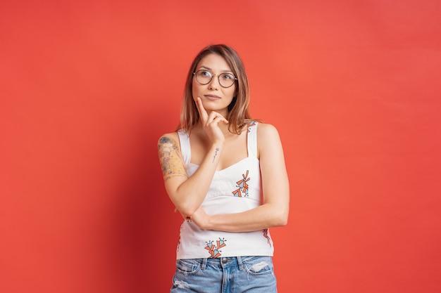 Kaukaska kobieta myśleć i wyobraźnia odizolowywająca na czerwieni ścianie z szkłami