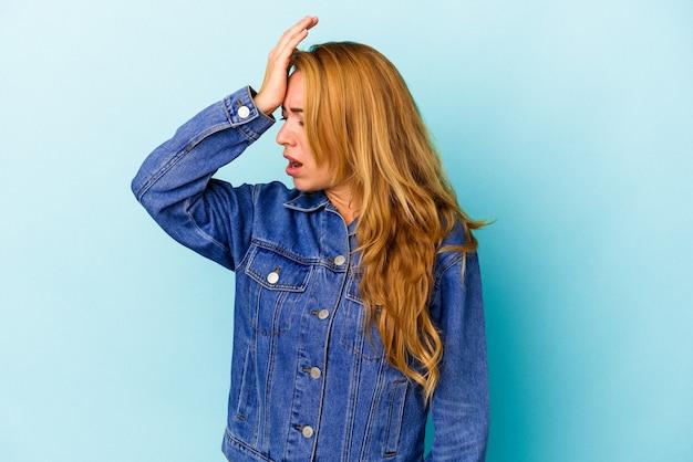 Kaukaska kobieta na białym tle na niebieskim tle zapominając o czymś, uderzając dłonią w czoło i zamykając oczy.