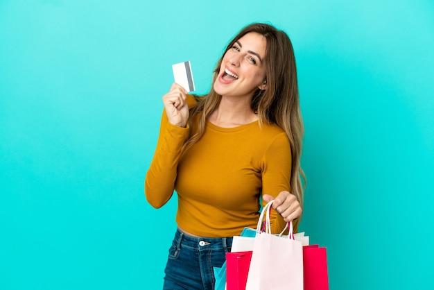 Kaukaska kobieta na niebieskim tle trzymająca torby na zakupy i kartę kredytową
