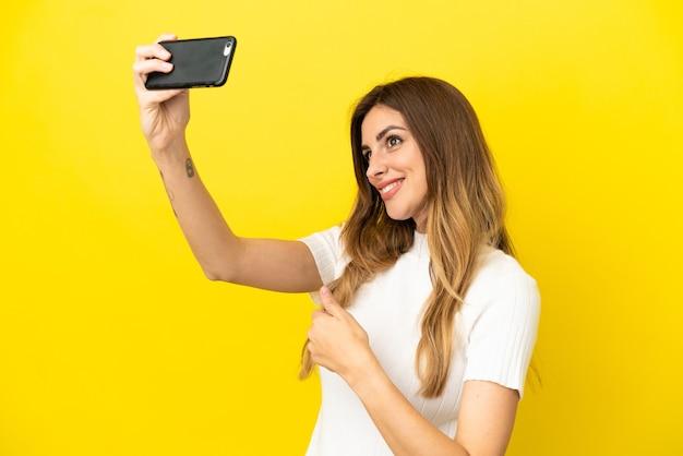 Kaukaska kobieta na żółtym tle robi selfie z telefonem komórkowym