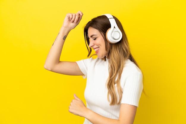 Kaukaska kobieta na żółtym tle słuchając muzyki i tańcząc