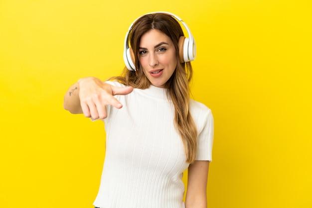 Kaukaska kobieta na żółtym tle słuchania muzyki