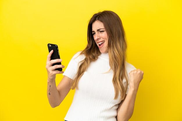 Kaukaska kobieta na żółtym tle, używająca telefonu komórkowego i wykonująca gest zwycięstwa victory