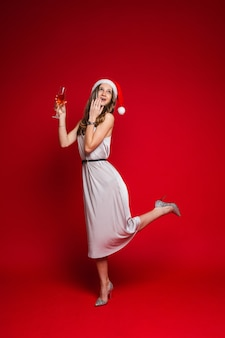Kaukaska kobieta o atrakcyjnym wyglądzie trzyma kieliszek białego wina, zdjęcie na czerwono
