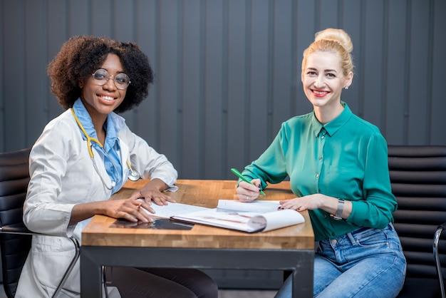 Kaukaska kobieta odbywa konsultację medyczną siedzącą z lekarzem pochodzenia afro w nowoczesnym biurze