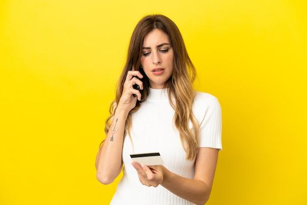 Kaukaska kobieta odizolowana na żółtym tle kupując za pomocą telefonu komórkowego za pomocą karty kredytowej