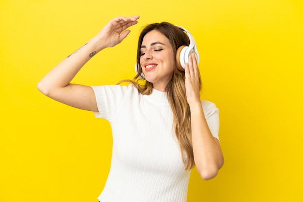 Kaukaska kobieta odizolowana na żółtym tle słuchając muzyki i tańcząc