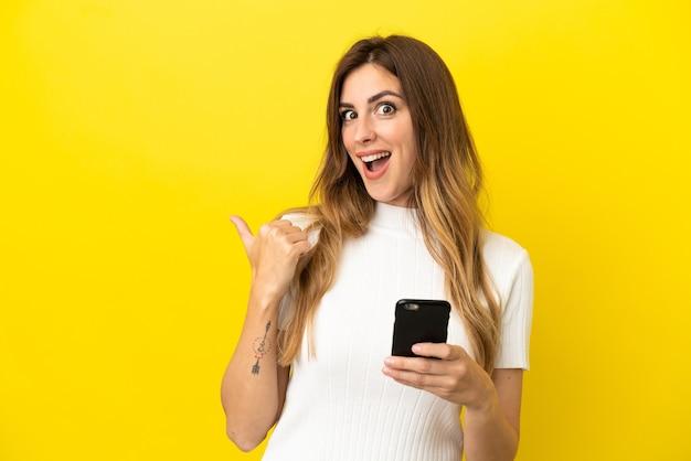 Kaukaska kobieta odizolowana na żółtym tle za pomocą telefonu komórkowego i wskazująca na bok