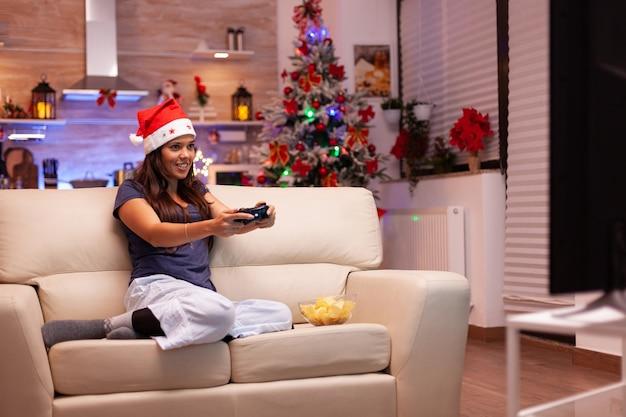 Kaukaska kobieta odpoczywa na kanapie, grając w gry wideo za pomocą joysticka do gier