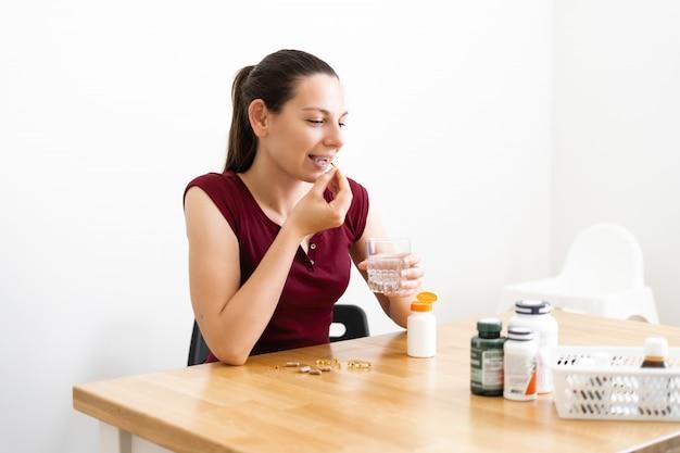 Kaukaska kobieta pije dużo pigułek. medycyna zapobiegawcza. suplementy diety