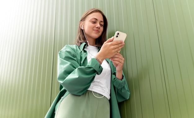 Kaukaska kobieta pisze do kogoś na swoim smartfonie