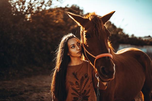 Kaukaska kobieta pozuje z brązowym koniem