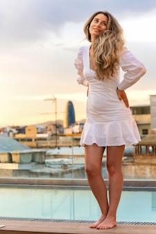 Kaukaska kobieta pozuje z widokiem na barcelonę w tle, hiszpania