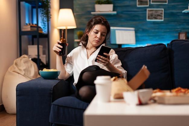 Kaukaska kobieta relaksuje się na kanapie przeglądając media społecznościowe za pomocą smartfona