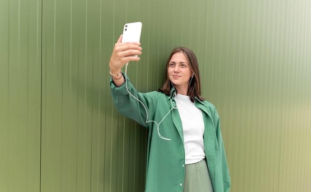 Kaukaska kobieta robi selfie swoim smartfonem