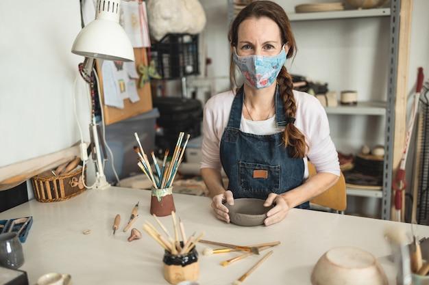 Kaukaska kobieta robiąca ceramiczny talerz do zupy podczas noszenia ochronnej maski na twarz w celu zapobiegania koronawirusowi - kobieta w pracy w swoim kreatywnym studiu ceramiki - skup się na twarzy